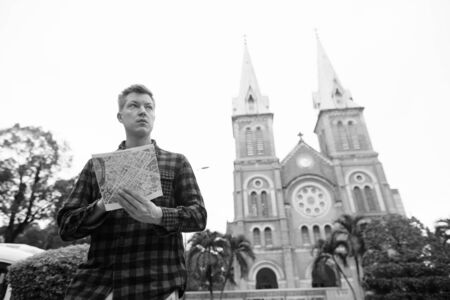 Young handsome tourist man looking at the map against view of the cathedral