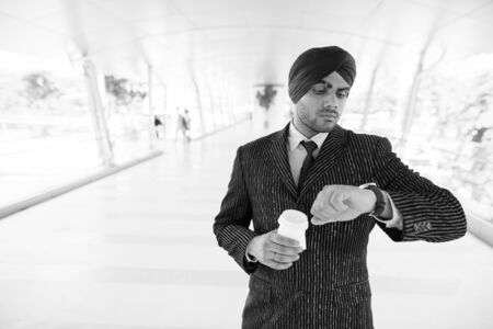 Young handsome Indian Sikh businessman waiting at the footbridge