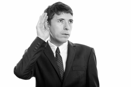 Portrait of businessman in suit thinking while listening Banque d'images