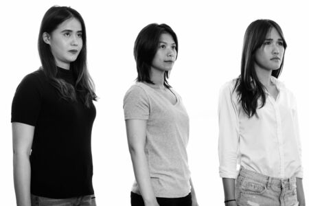 Studio shot of three young Asian woman friends thinking