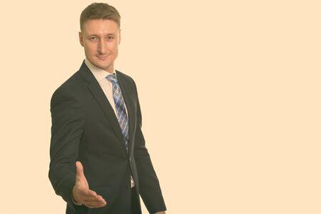Portrait d'un bel homme d'affaires heureux en costume donnant une poignée de main Banque d'images