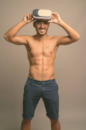Young handsome Persian man shirtless against gray background