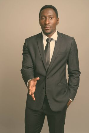Young handsome African businessman against gray background Banque d'images