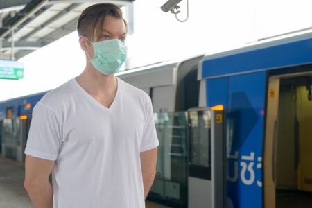 Young man thinking with mask for protection from corona virus outbreak at the train station
