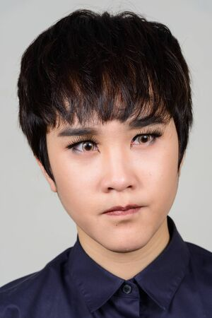 Face of stressed young androgynous Asian woman Stock Photo
