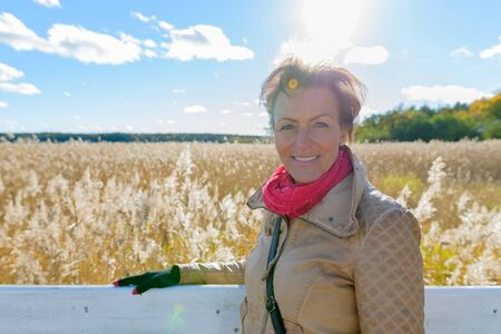 Happy beautiful mature woman smiling against scenic view of autumn bulrush field Banque d'images