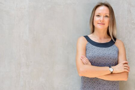 Happy blonde businesswoman smiling with arms crossed against concrete wall Stock Photo