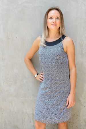 Happy beautiful blonde businesswoman thinking against concrete wall