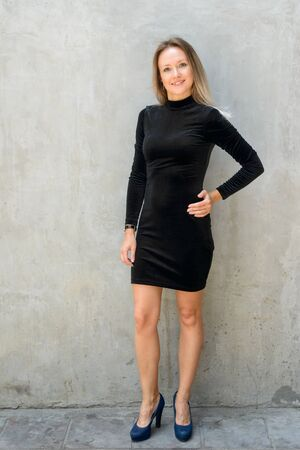 Full body shot of happy beautiful blonde businesswoman smiling against concrete wall