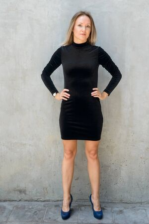 Full body shot of beautiful blonde businesswoman against concrete wall