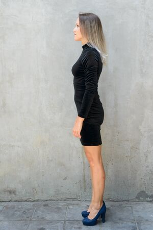 Full body shot profile view of beautiful blonde businesswoman against concrete wall