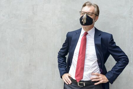 Mature businessman in suit thinking and wearing mask against concrete wall Stock Photo