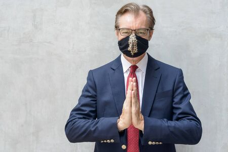 Mature businessman in suit wearing mask and greeting with respect against concrete wall Stock Photo