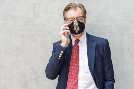 Mature businessman wearing mask and talking on the phone against concrete wall