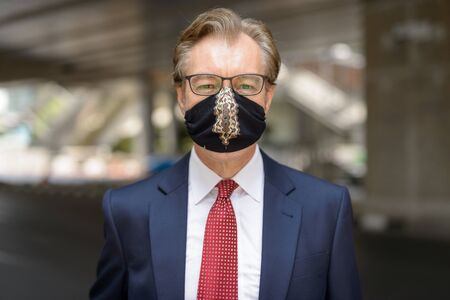 Face of mature businessman wearing mask for protection from corona virus outbreak in the city streets Stock Photo
