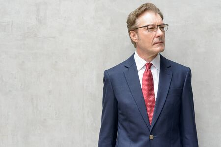 Handsome mature businessman in suit wearing eyeglasses and thinking outdoors
