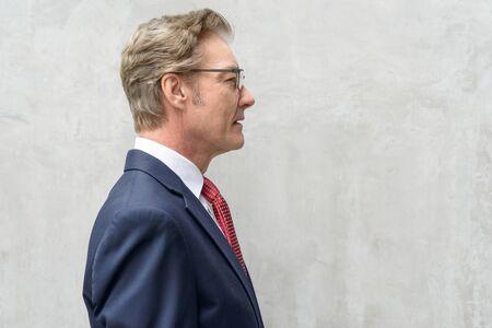 Closeup profile view of handsome mature businessman against concrete wall