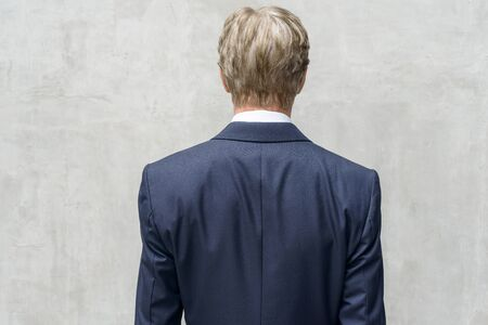 Rear view of mature businessman in suit against concrete wall