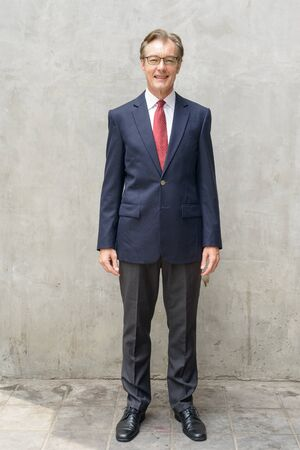 Full body shot of happy handsome mature businessman smiling against concrete wall