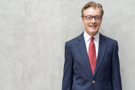 Happy handsome mature businessman in suit smiling against concrete wall Stock Photo