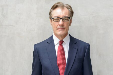 Face of handsome mature businessman with eyeglasses against concrete wall Stock Photo
