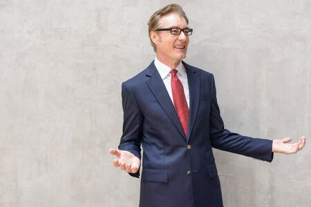 Happy handsome mature businessman in suit talking outdoors