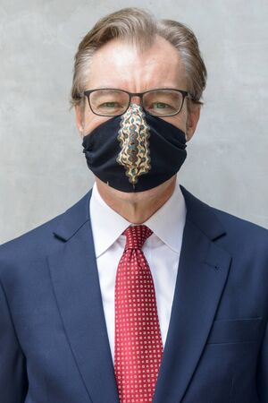 Face of mature businessman with mask for protection from coronavirus outbreak against concrete wall