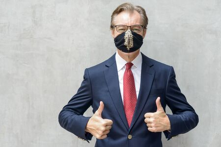 Mature businessman in suit wearing mask and giving thumbs up against concrete wall