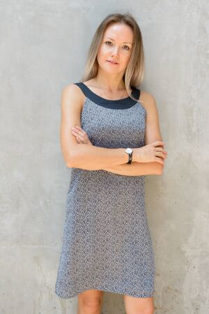 Beautiful blonde businesswoman with arms crossed against concrete wall