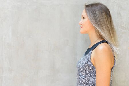 Closeup profile view of beautiful blonde businesswoman against concrete wall Stock Photo
