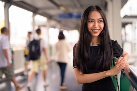 Happy young beautiful Asian tourist woman thinking on the footbridge