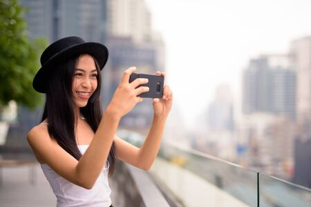 Happy young beautiful Asian tourist woman taking picture with phone against view of the city
