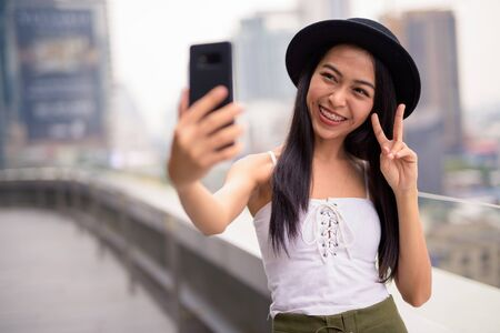 Happy young beautiful Asian tourist woman taking selfie against view of the city