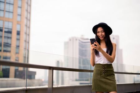 Happy young beautiful Asian tourist woman using phone against view of the city