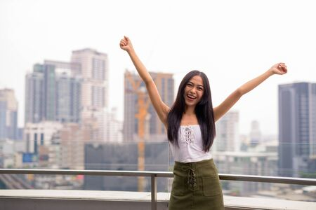 Happy young beautiful Asian tourist woman against view of the city Stock Photo