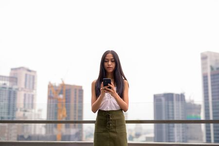 Young beautiful Asian tourist woman using phone against view of the city