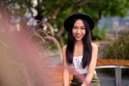 Happy young beautiful Asian tourist woman at the rooftop garden