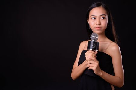 Portrait of young beautiful Asian woman using microphone