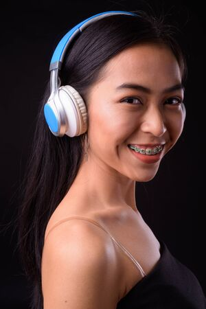 Face of happy young beautiful Asian woman listening to music Stock Photo