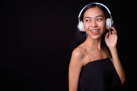 Portrait of happy young beautiful Asian woman listening to music