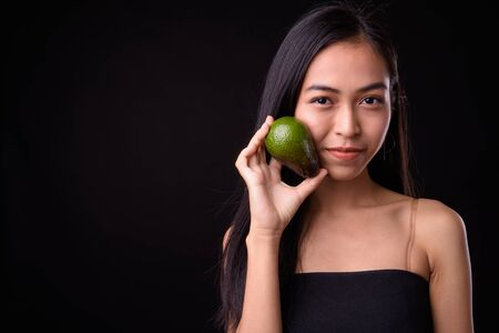 Face of young beautiful Asian woman holding avocado Stock Photo