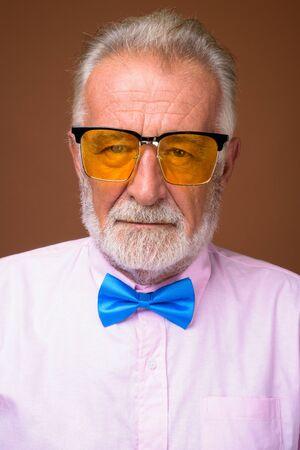 Senior handsome man wearing stylish clothes against brown backgr Banque d'images