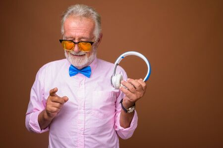 Studio shot of senior handsome man wearing stylish clothes against brown background 免版税图像