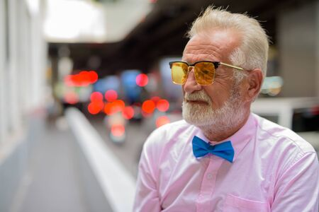 Portrait of handsome senior tourist man wearing stylish clothes while exploring the city of Bangkok, Thailand 免版税图像