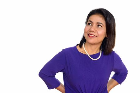 Studio shot of happy mature Asian woman thinking isolated against white background