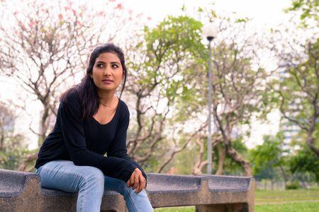 Young beautiful Persian woman thinking at the park Standard-Bild