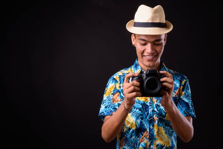 Portrait of happy young Indian tourist man taking picture with camera