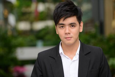 Face of young handsome Asian businessman at the park Foto de archivo