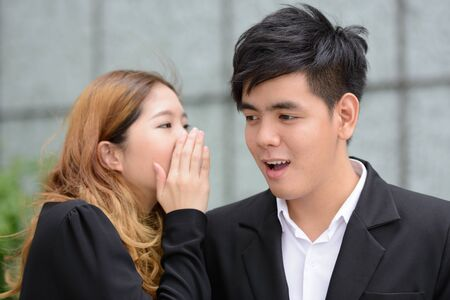 Young Asian business couple whispering together in the city
