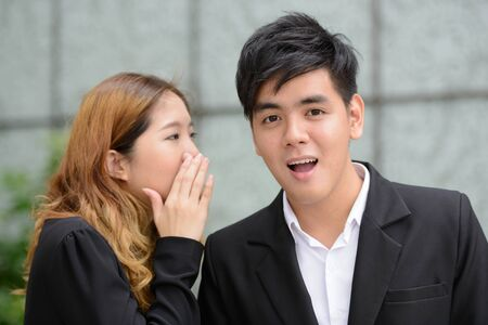 Young Asian business couple whispering together in the city Banque d'images
